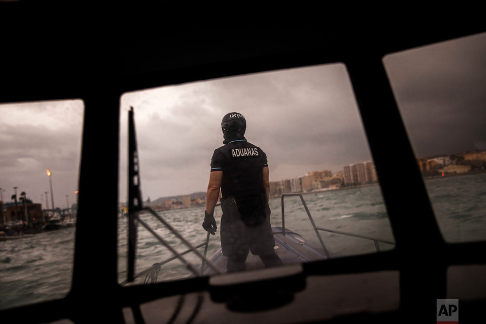 In this Wednesday, Feb. 28, 2018 photo, Spain's Customs Surveillance Service officer sails near the port of Algeciras, in Cadiz province, south of Spain.  (AP Photo/Emilio Morenatti)