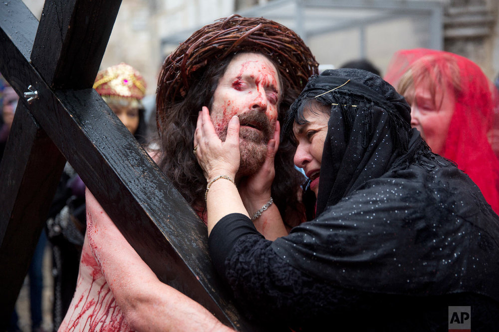 An actor dressed as Jesus Christ carries a cross as he reenacts the crucifixion walk along the Via Dolorosa towards the Church of the Holy Sepulchre, traditionally believed by many to be the site of the crucifixion of Jesus Christ, during the Good Friday procession in Jerusalem's Old City in Jerusalem, Friday, March 30, 2018. (AP Photo/Ariel Schalit)
