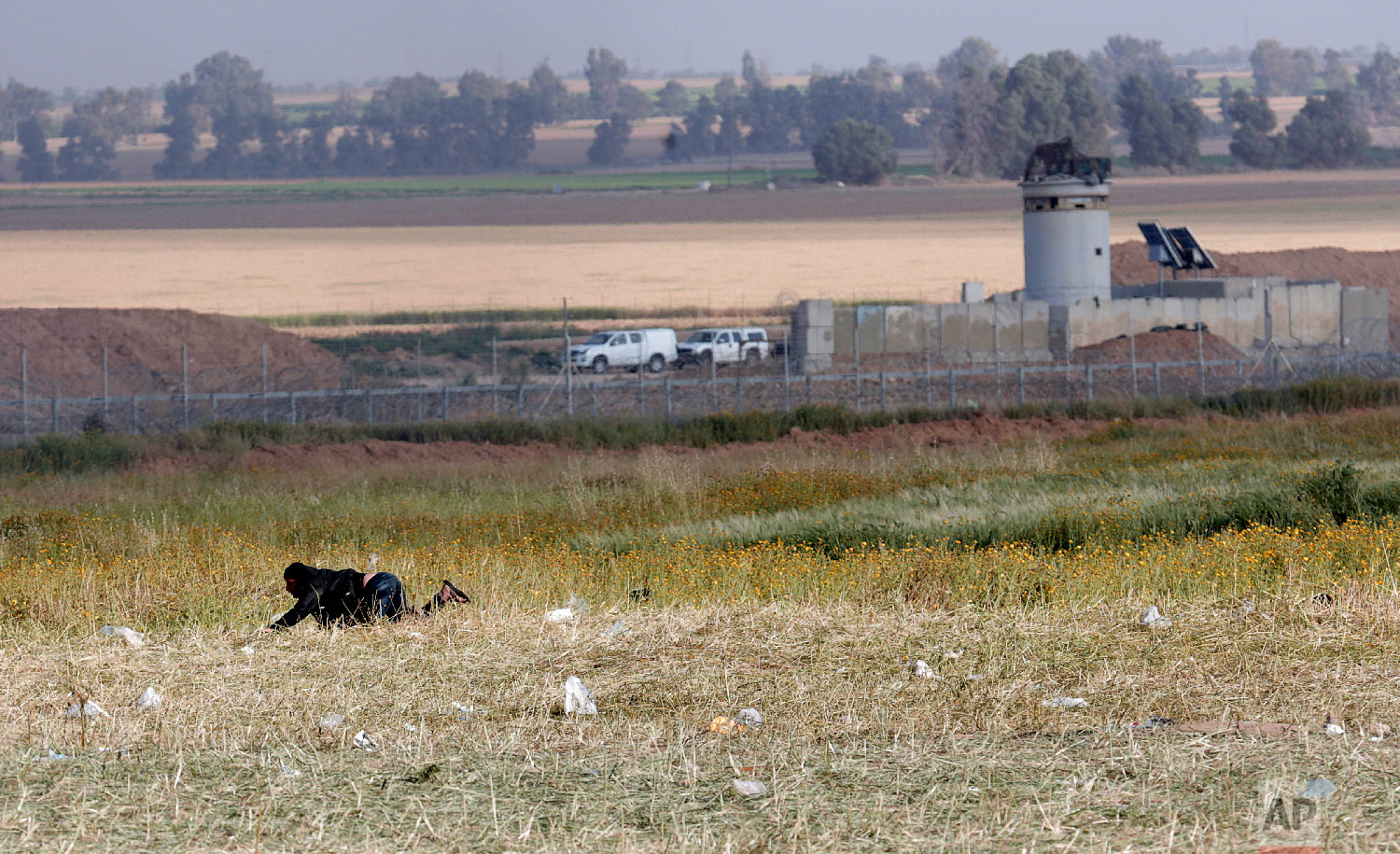 A Palestinian protester crawls during clashes with Israeli troops along the Gaza Strip border with Israel, east of Khan Younis, Gaza Strip, Friday, March 30, 2018. (AP Photo/Adel Hana)
