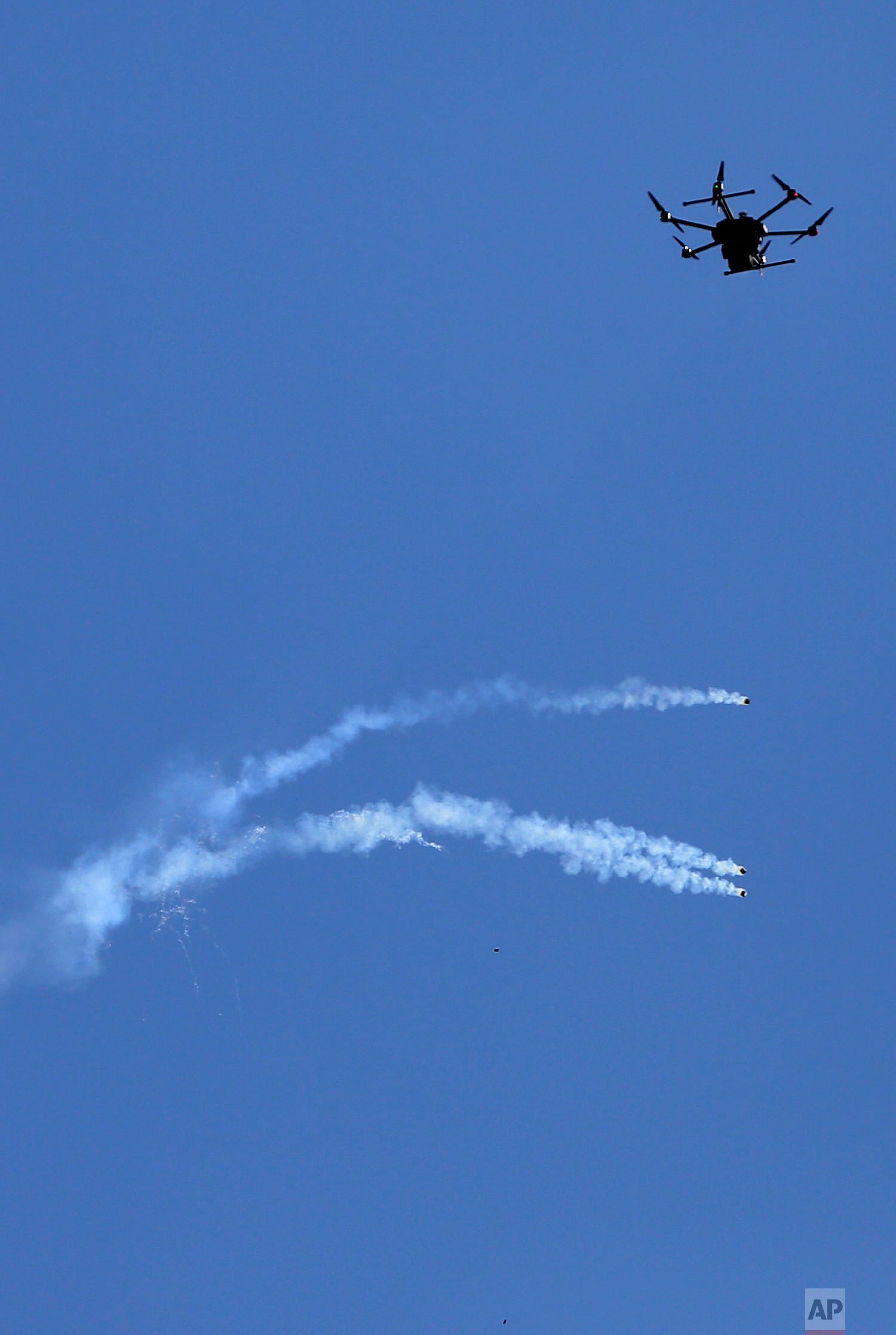 A drone used by Israeli troops fires teargas at Palestinians during a demonstration near the Gaza Strip border with Israel, in eastern Gaza City, Friday, March 30, 2018. (AP Photo/ Khalil Hamra)