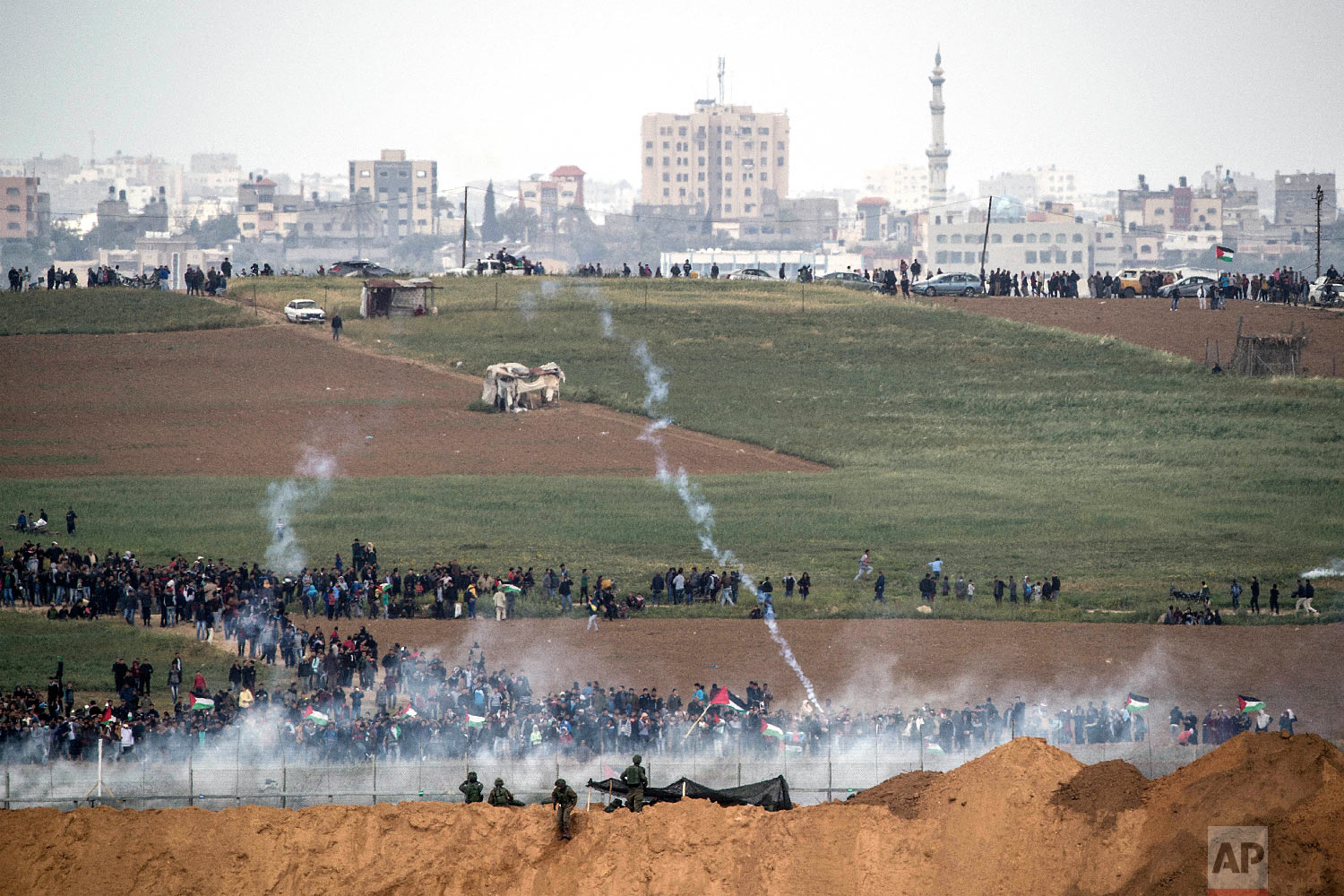 Israeli soldiers shoot tear gas toward Palestinian protesters as they gather on the Israel Gaza border, Friday, March 30, 2018. (AP Photo/Tsafrir Abayov)