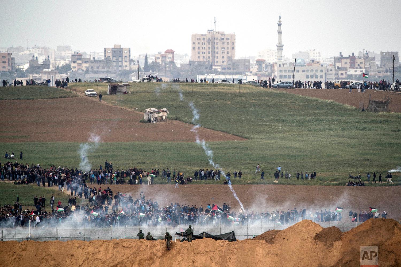 Israeli soldiers shoot tear gas toward Palestinian protesters as they gather on the Israel Gaza border, Friday, March 30, 2018. (AP Photo/Tsafrir Abayov)