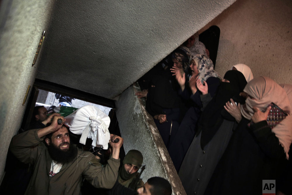 Relatives of Palestinian Ziyad Al-hawajri, react as mourners carry his body into the family house during his funeral in Nuseirat, central Gaza Strip, Thursday, March 22, 2018. Al-hawajri, is one of the two members of Hamas security forces who were killed Thursday during an operation to arrest suspects wanted for a bombing that targeted the visiting Palestinian premier's convoy in Gaza last week. (AP Photo/ Khalil Hamra)