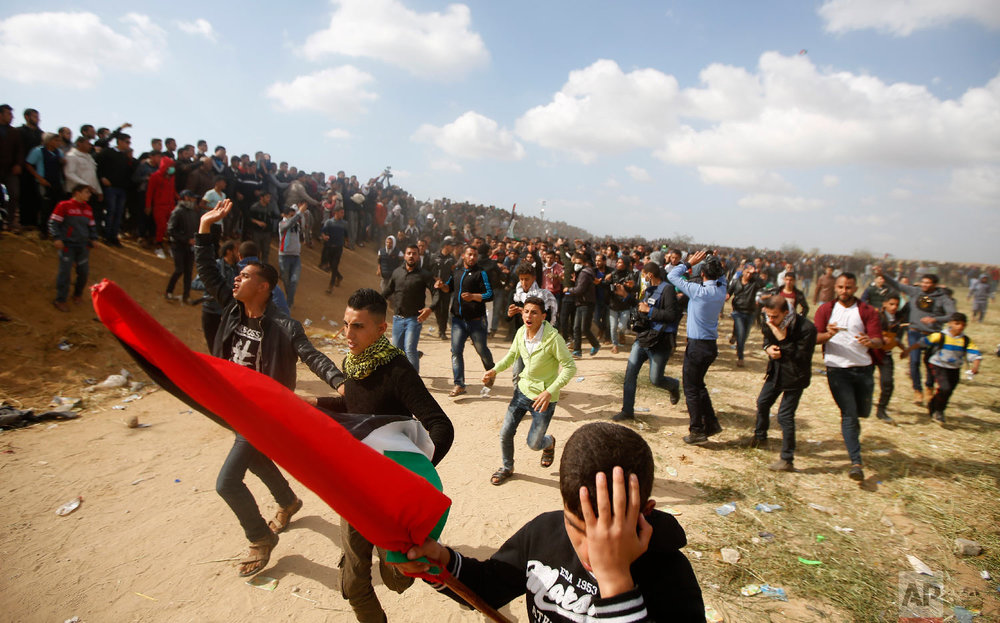 Palestinian protesters react while evacuate a wounded youth during clashes with Israeli troops along the Gaza Strip border with Israel, east of Khan Younis, Gaza Strip, Friday, March 30, 2018. (AP Photo/Adel Hana)