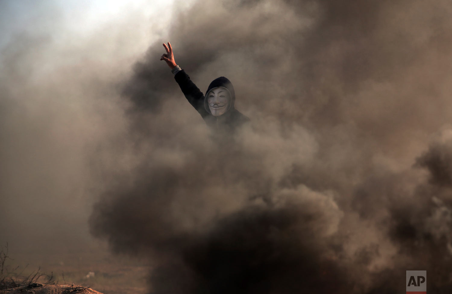A Palestinian protester flashes the V sign during a protest near the Gaza Strip border with Israel, in eastern Gaza City, Saturday, March 31, 2018. (AP Photo/ Khalil Hamra)