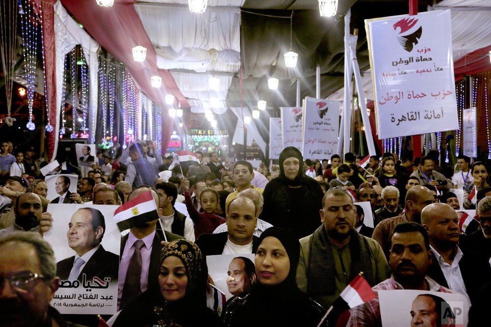 Supporters of Egyptian presidential candidate President Abdel-Fattah el-Sissi hold campaign posters during a campaign rally, near the Gamaleya district of Cairo, where el-Sissi was born, in front of al-Hussein Mosque, Egypt, Monday, March 19, 2018. (AP Photo/Nariman El-Mofty)