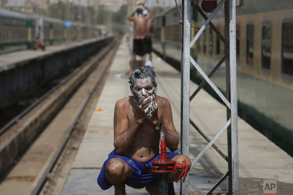 Pakistan railway employees cool themselves off during a hot afternoon in Karachi, Pakistan, Wednesday, March 28, 2018. People experience warm weather, with the temperatures reaching 39 degree Celsius (102 Fahrenheit). (AP Photo/Fareed Khan)