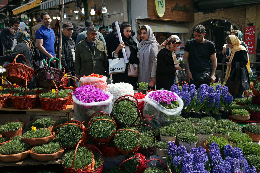 In this Monday, March 19, 2018 photo, Iranians shop for hyacinths, garlic, sprouts and other items used to celebrate the Iranian New Year, ahead of the holiday, at the Tajrish traditional bazaar in northern Tehran, Iran. (AP Photo/Vahid Salemi)