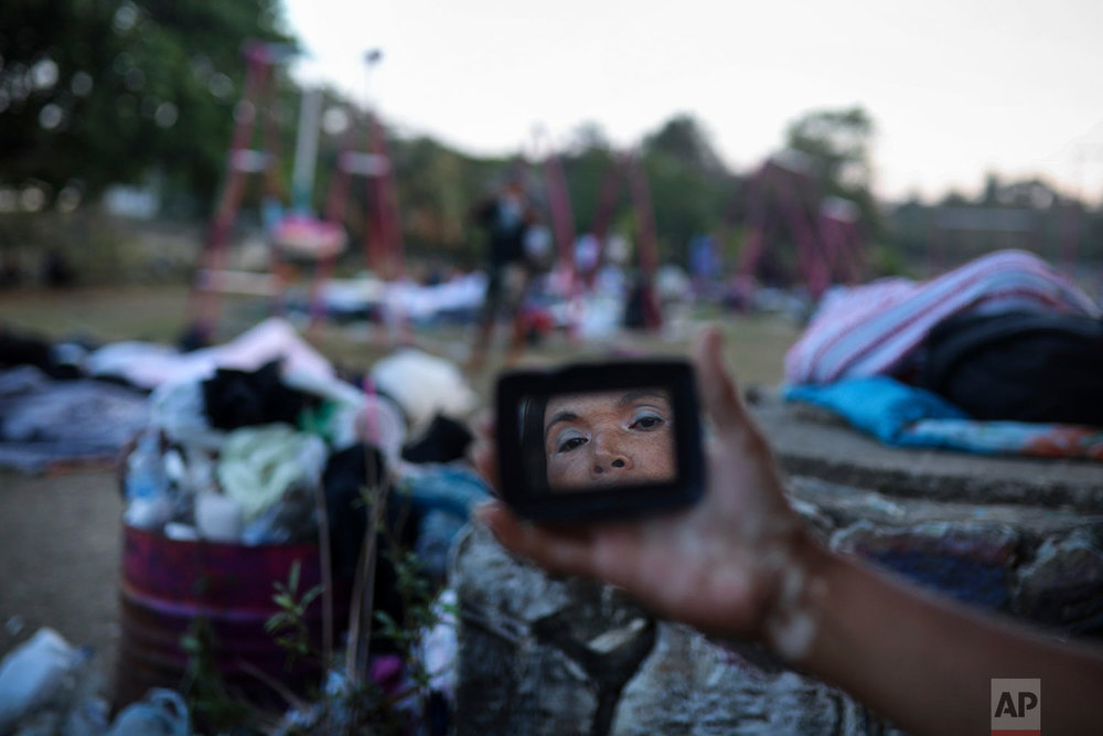A Central American migrant woman is reflected in a mirror as she gets ready for the day while traveling with the annual Migrant Stations of the Cross caravan in Matias Romero, Oaxaca State, Mexico, early Tuesday, April 3, 2018. (AP Photo/Felix Marquez)