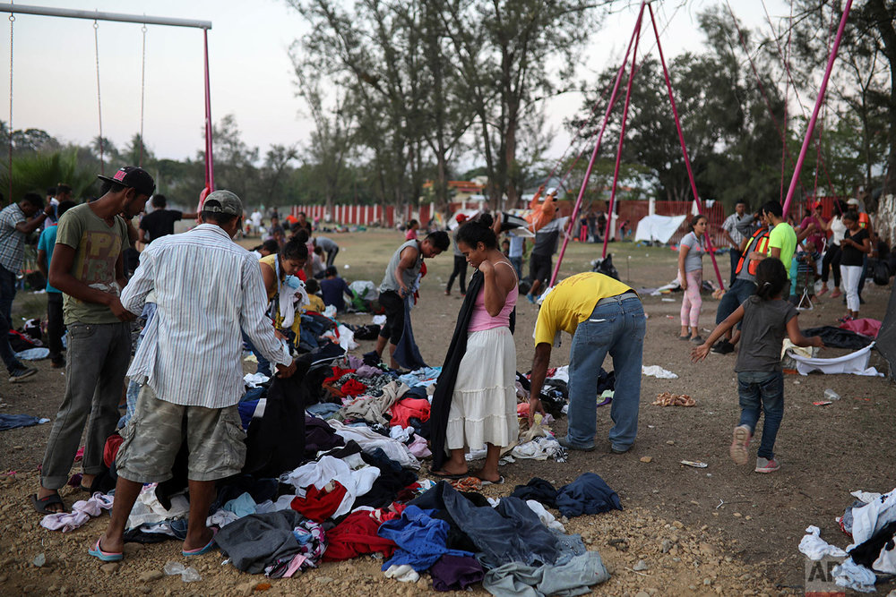 Central American migrants participating in the Migrant Stations of the Cross caravan search through donated clothing during the caravan's stop at a sports center in Matias Romero, Oaxaca state, Mexico, late Monday, April 2, 2018. (AP Photo/Felix Marquez)