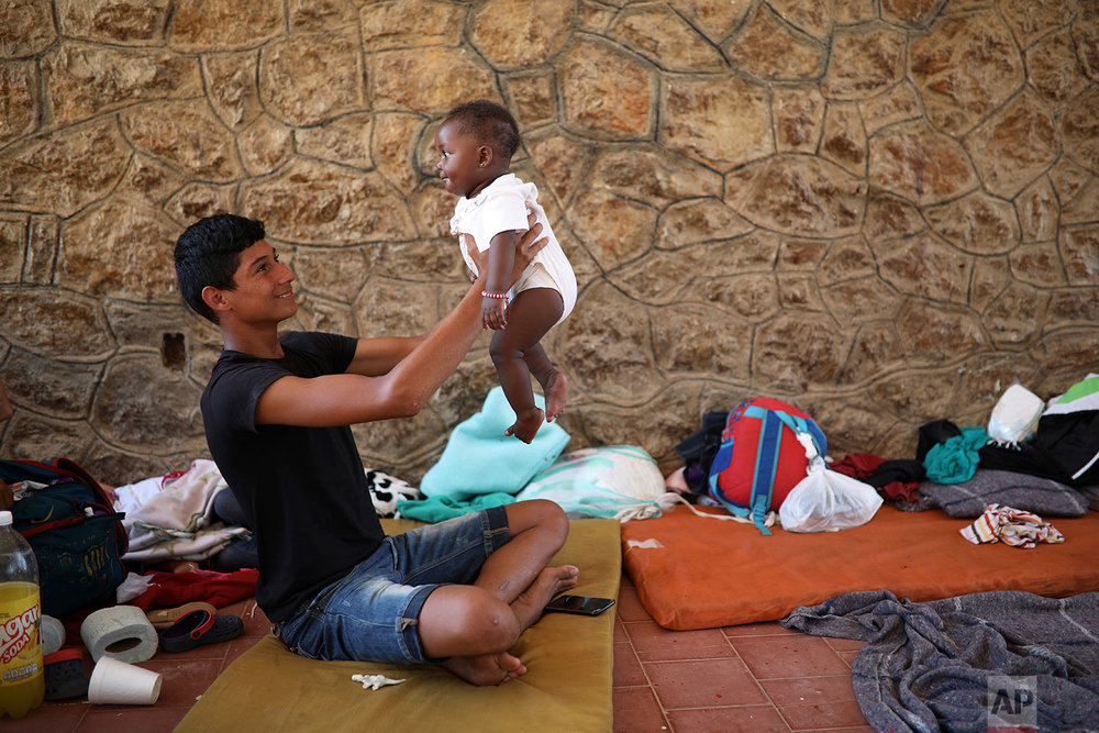 A Central American migrant plays with a baby during a stop by the Migrant Stations of the Cross caravan, inside a sports center in Matias Romero, Oaxaca state, Mexico, Monday, April 2, 2018. (AP Photo/Felix Marquez)