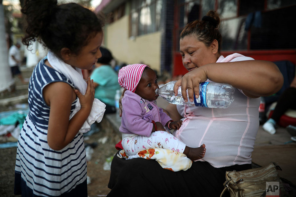 A Central American migrant woman gives water to a baby as the annual Migrant Stations of the Cross caravan sets up camp at a sports center in Matias Romero, Oaxaca state, Mexico, late Monday, April 2, 2018. (AP Photo/Felix Marquez)