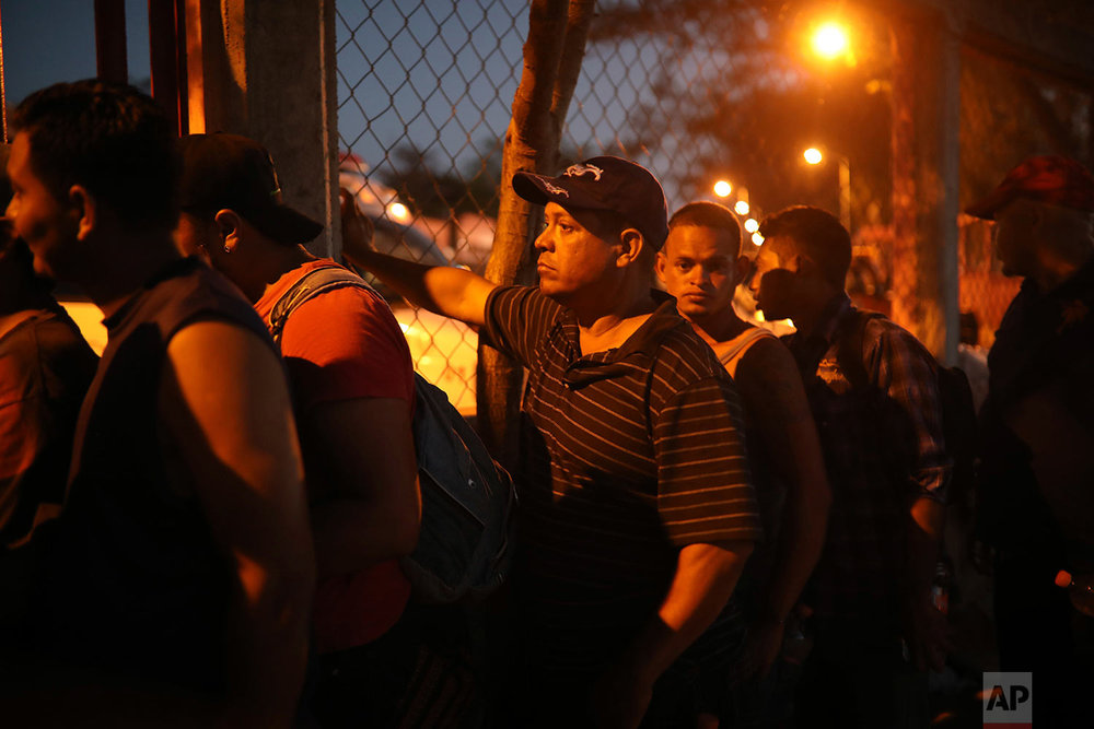 Central American migrant men stand in line for food during the annual Migrant Stations of the Cross caravan as the caravan makes a stop at a sports center in Matias Romero, Oaxaca state, Mexico, late Monday, April 2, 2018. (AP Photo/Felix Marquez)