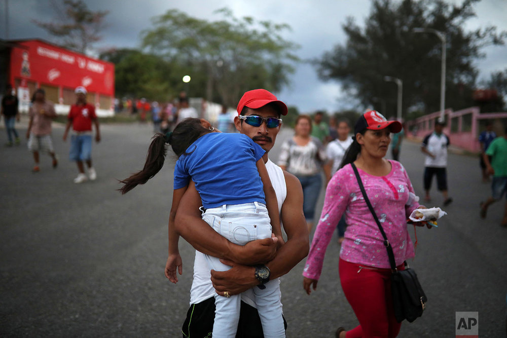 A Honduran man carries a sleeping girl, as Central American migrants traveling with the annual Stations of the Cross caravan march to call for migrants' rights and protest the policies of U.S. President Donald Trump and Honduran President Juan Orlando Hernandez, in Matias Romero, Oaxaca State, Mexico, Tuesday, April 3, 2018. (AP Photo/Felix Marquez)