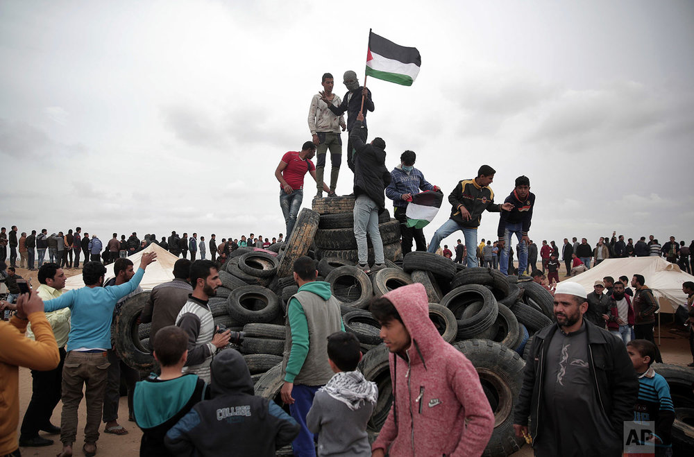 A protester holds a Palestinian flag on top of tires to be burned during an ongoing protest next to Gaza's border with Israel, east of Khan Younis, Gaza Strip, Tuesday, April 3, 2018. (AP Photo/Khalil Hamra)