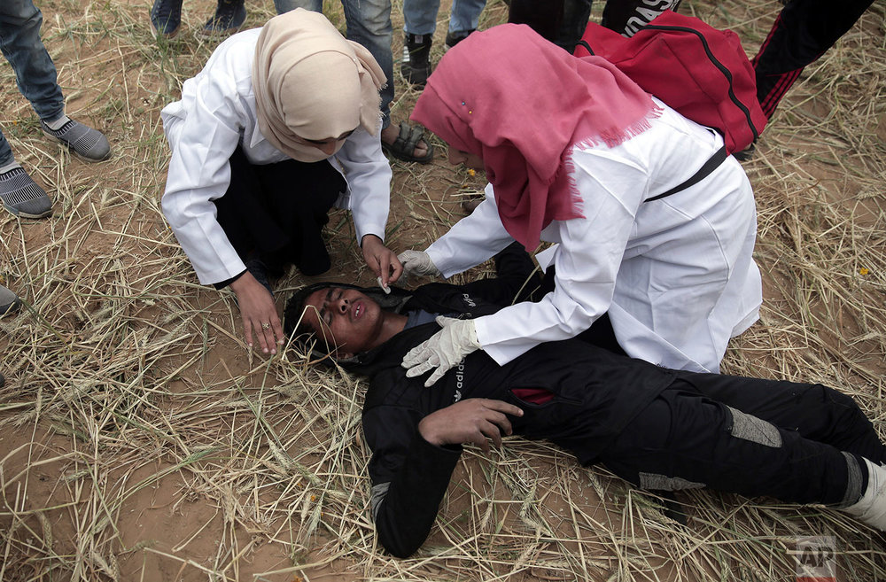 Palestinian medics treat a wounded protester during a protest next to Gaza's border with Israel, east of Khan Younis, Gaza Strip, Tuesday, April 3, 2018. (AP Photo/Khalil Hamra)
