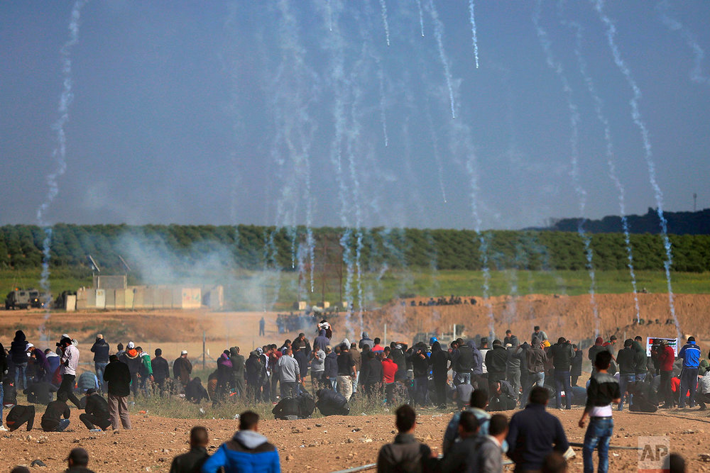 Teargas canisters fired by Israeli troops fall down on Palestinians during a demonstration near the Gaza Strip border with Israel, in eastern Gaza City, Friday, March 30, 2018. (AP Photo/Khalil Hamra)