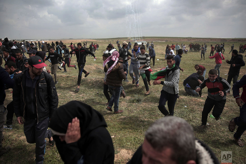Palestinian protesters run for cover from teargas fired by Israeli troops during a demonstration near the Gaza Strip border with Israel, in eastern Gaza City, Friday, March 30, 2018. (AP Photo/Khalil Hamra)