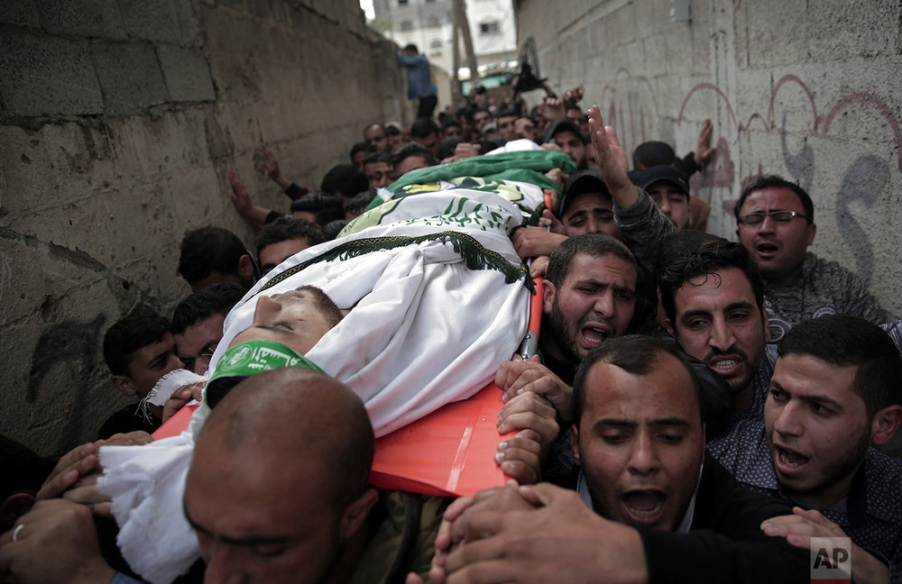 Palestinian mourners carry the body of 23-year-old Mojahid al-Khodari, who was killed early Thursday morning by an Israeli airstrike, during his funeral in Gaza City, Thursday, April 5, 2018. (AP Photo/Khalil Hamra)