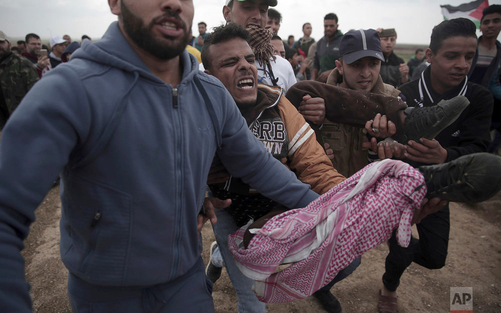 Palestinian protesters carry a wounded man who was shot by Israeli troops during a demonstration near the Gaza Strip border with Israel in eastern Gaza City, Friday, March 30, 2018. (AP Photo/ Khalil Hamra)
