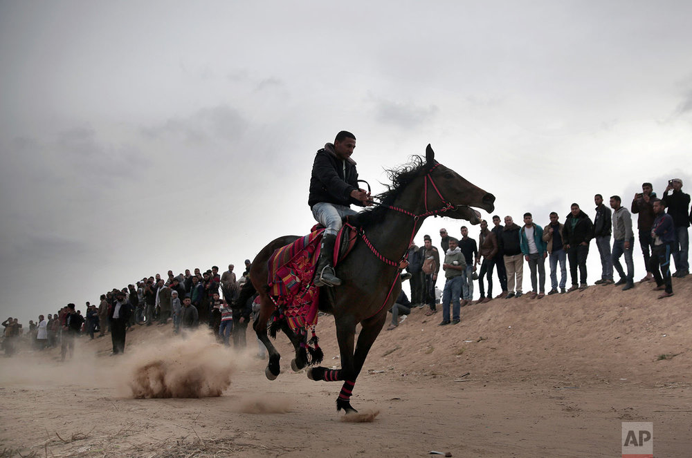 A Palestinian rides a horse past demonstrators during a protest next to Gaza's border with Israel, east of Khan Younis, Gaza Strip, Tuesday, April 3, 2018. (AP Photo/Khalil Hamra)