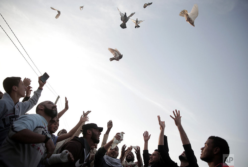 Palestinian protesters fly pigeons during a protest at the Gaza Strip border with Israel, in eastern Gaza City, Wednesday, April 4, 2018. A leading Israel human rights group urged Israeli forces in a rare step Wednesday to disobey open-fire orders unless Gaza protesters pose an imminent threat to soldiers' lives. (AP Photo/Khalil Hamra)