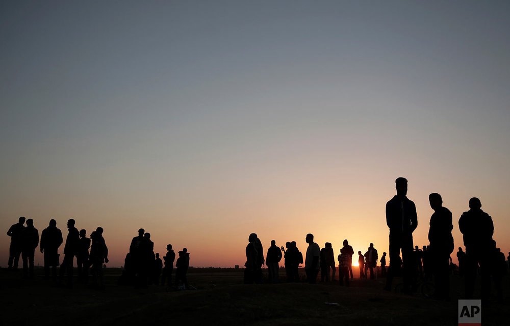The sun sets over Palestinian protesters gathered at the Gaza Strip border with Israel, in eastern Gaza City, Sunday, April 1, 2018. (AP Photo/Khalil Hamra)