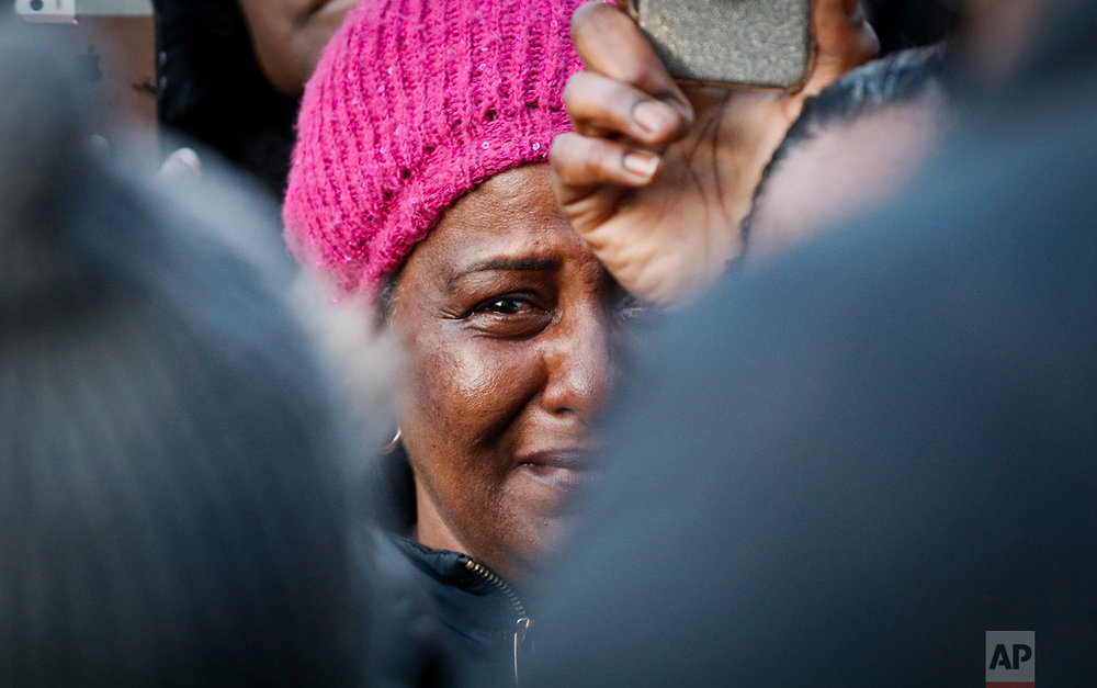 A woman cries as she listens to Lorna Vassell address a rally for son Saheed Vassell, fatally shot by police Wednesday, in the Crown Heights section of Brooklyn borough in New York on Thursday, April 5, 2018. (AP Photo/Bebeto Matthews)