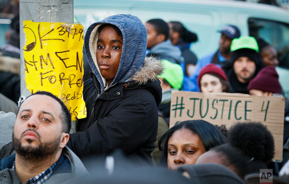 A youngster climbs a lamppost to listen to speakers at a rally for Saheed Vassell, a 34-year-old welder and father of a teenage son who was fatally shot by New York Police  (AP Photo/Bebeto Matthews)