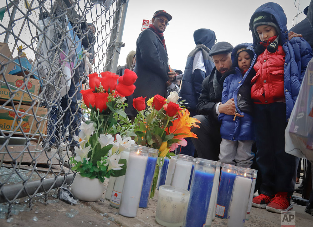 Rev. Kirsten Foy, National Action Network's Northeast regional director, center, with his sons, Seth, 7, far right, and and Samuel, 5, second from right, pray at a memorial, Thursday, April 5, 2018, in the Brooklyn borough of New York, where Saheed Vassell was shot by police a day earlier. (AP Photo/Bebeto Matthews)