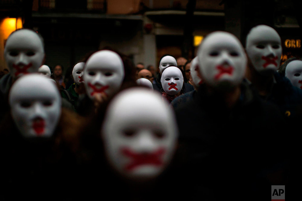 People wear white masks in support of Catalonian politicians jailed on charges of sedition and condemning the arrest of Catalonia's former president, Carles Puigdemont, in Germany, during a protest in Figures, Spain, Thursday, April. 5, 2018. A German court has ruled that former Catalan leader Carles Puigdemont can be released on bail pending a decision on his possible extradition to Spain. (AP Photo/Emilio Morenatti)