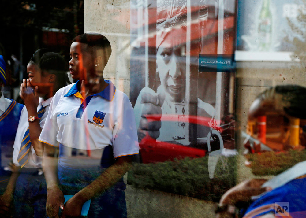 Seen through glass, school children pose for photos in front of a portrait of Winnie Madikizela-Mandela at the Mandela House Museum in Soweto, South Africa, Thursday, April 5, 2018. Madikizela-Mandela, the South African anti-apartheid activist and ex-wife of former President Nelson Mandela, who died earlier this week after a long illness, will be remembered at a memorial service on April 11, with her funeral three days later. (AP Photo/Denis Farrell)