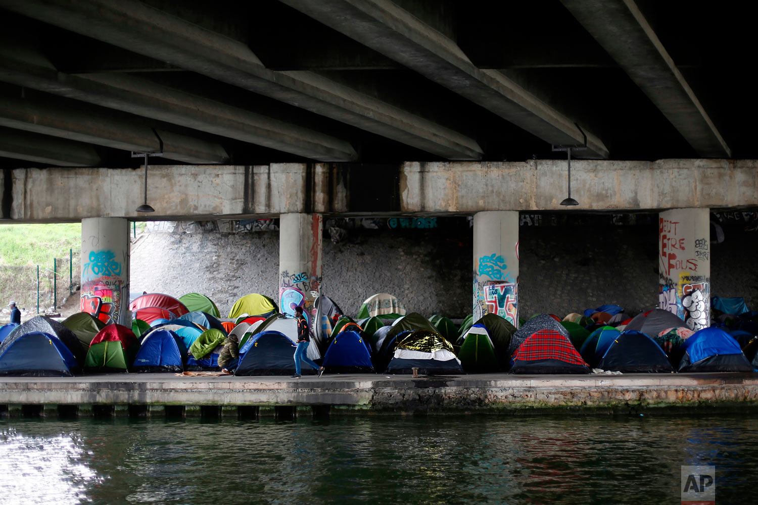 A migrant walks by tents in a makeshift camp along the Canal Saint Denis, in Paris, Wednesday, April 4, 2018. (AP Photo/Thibault Camus)