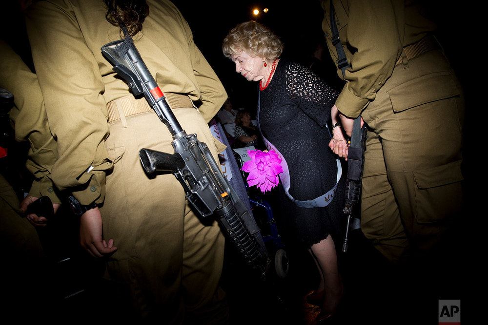 Holocaust survivor walks on the stage with the assistance of an Israeli soldier during a Beauty Heroines event in Ramat Gan, Israel, Monday, April 9, 2018.  (AP Photo/Oded Balilty)