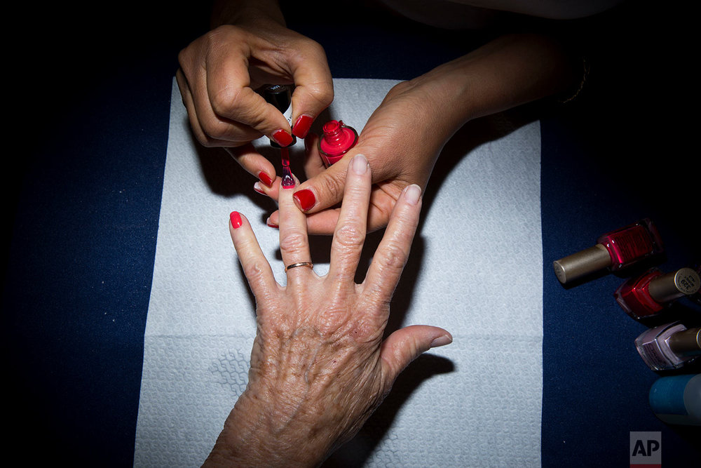 Holocaust survivor Hannah Beker, 79, has fingernail polish applied during a Beauty Heroines event in Ramat Gan, Israel, Monday, April 9, 2018.  (AP Photo/Oded Balilty)