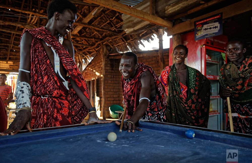 In this Friday, March 23, 2018 photo, young Maasai men relax and play a game of pool at a bar by the side of the road in the late afternoon at Mkata junction, near Mikumi National Park in Tanzania Friday, March 23, 2018. (AP Photo/Ben Curtis)