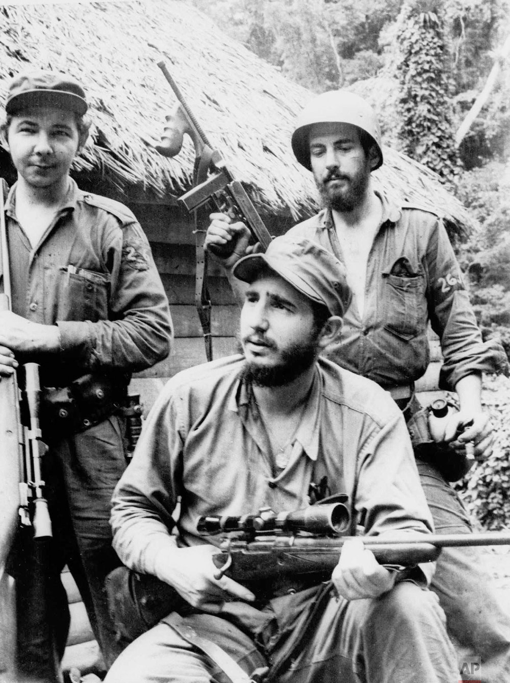Fidel Castro, the young anti-Batista guerrilla leader, center, his brother Raul Castro, left, and Camilo Cienfuegos, pose for a photo while in the mountains of eastern Cuba, March 14, 1957. Fidel led his young guerrillas to an improbable victory in 1959. (AP Photo/Andrew St. George)
