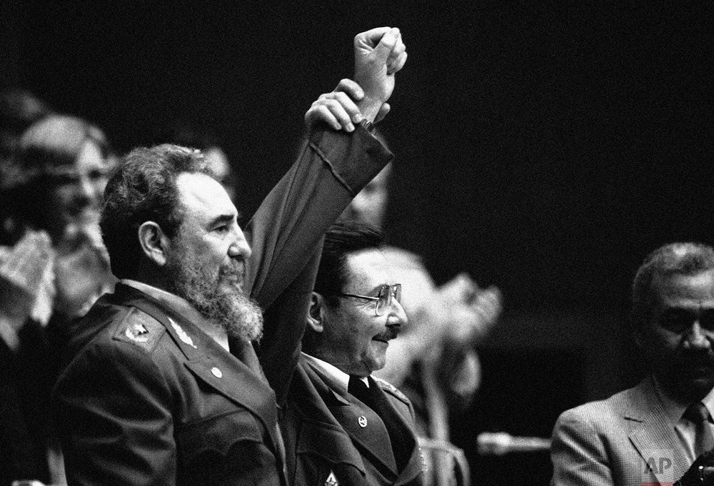 "Cuban President Fidel Castro, left, joins hands with his younger brother Raul Castro, chief of the Cuban Armed Forces and first vice president, after the two were reelected in the Third Cuban Communist Party Congress session in Havana, Feb. 8, 1986. Fidel ruled for nearly five decades as Cuba's ""Maximum Leader"". (AP Photo/Charles Tasnadi)"