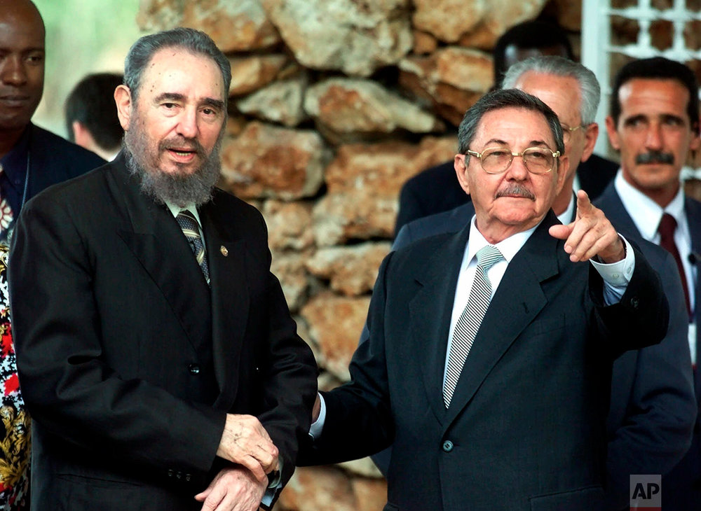 Cuban President Fidel Castro and his brother Raul Castro, first vice president and head of the Cuban Armed Forces, wait for heads of state at an official lunch for visiting leaders of the Group 77 Summit in Havana, April 13, 2000. The brothers rarely appeared in public together and even less out of military uniform. (AP Photo/Jose Goitia)