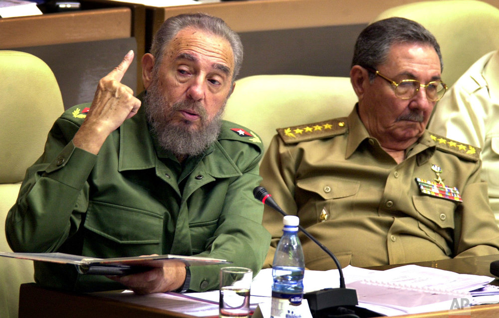 Cuban President Fidel Castro, left, seated next to his brother Defense Minister Raul Castro and first Vice President, speaks during the inauguration of the ninth session of the National Assembly, in Havana, Nov. 2, 2002. Fidel's commitment to socialism never wavered. (AP Photo/Cristobal Herrera)