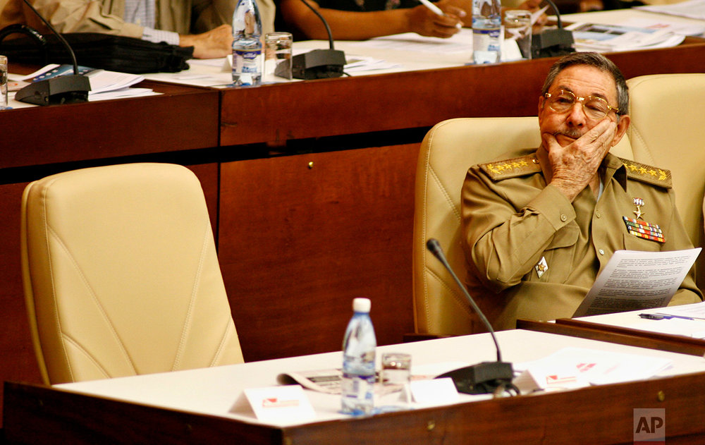 Cuba's acting President Raul Castro sits next to the chair usually occupied by his older brother Fidel Castro, at a parliament year-end session in Havana, Dec. 22, 2006. A severe gastrointestinal illness in 2006 nearly killed Fidel, forcing him to turn power over to his younger brother. (AP Photo/Javier Galeano)