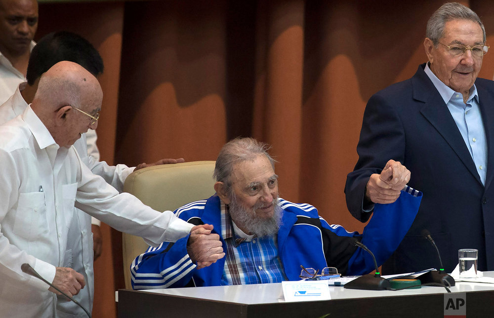 Fidel Castro, supported by Cuban President Raul Castro, right, and second secretary of the Central Committee, Jose Ramon Machado Ventura, makes a rare public appearance at the closing ceremonies of the 7th Congress of the Cuban Communist Party, in Havana, April 19, 2016. Castro came to say goodbye to the Communist Party he put in power a half-century ago. (Ismael Francisco/Cubadebate via AP)