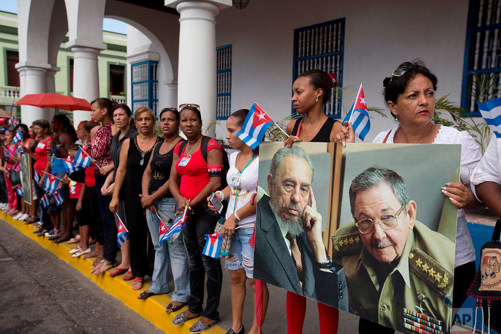 Women hold a portrait of the late Fidel Castro, and of his brother Cuba's President Raul Castro, as they wait to see the arrival of the caravan transporting Fidel's ashes from Havana, in Santiago, Cuba, Dec. 3, 2016. (AP Photo/Ricardo Mazalan)