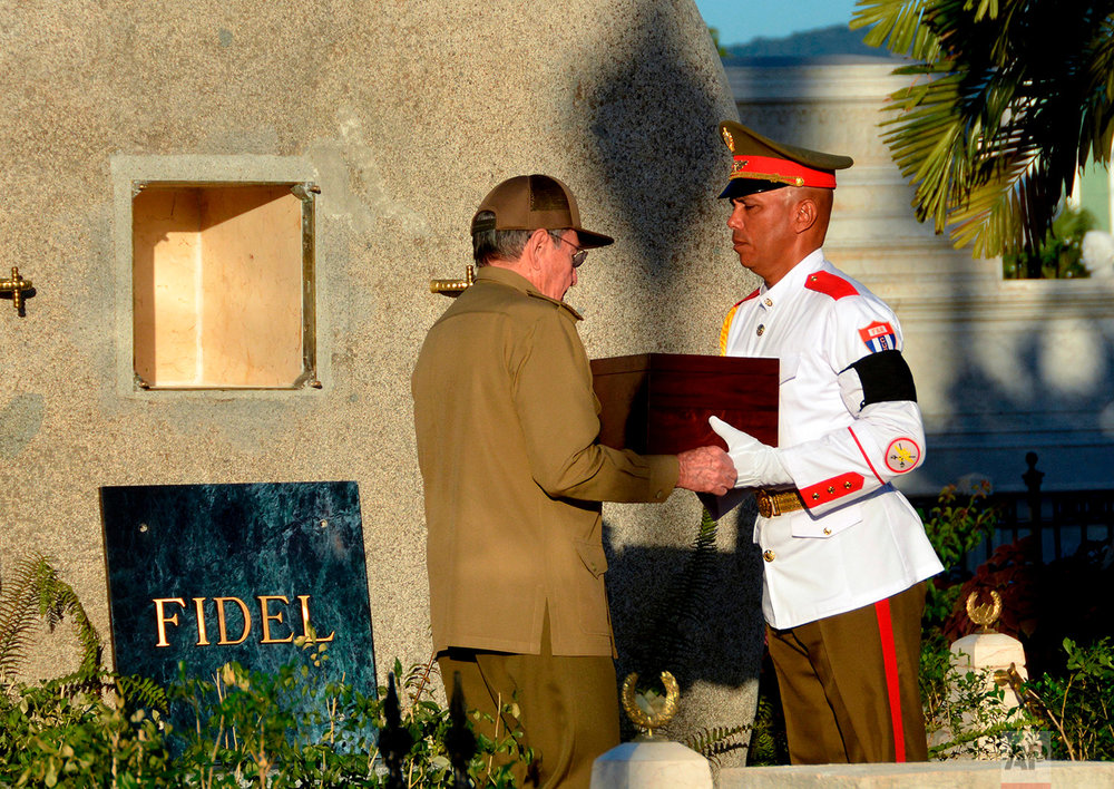 Cuba's President Raul Castro receives the ashes of his older brother Fidel Castro from an honor guard before placing them into a niche in his tomb, at the Santa Ifigenia cemetery in Santiago, Cuba, Dec. 4, 2016. The tomb stands to the side of a memorial to the rebel soldiers killed in an attack that the Castros led on Santiago's Moncada barracks on July 26, 1953. (Marcelino Vazquez Hernandez/ACN via AP)
