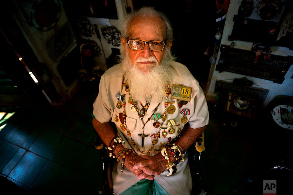 In this April 12, 2018 photo, artist and former diplomat Hector Pascual Gallo Portieres poses at his home in the Alamar public housing complex in Havana, Cuba. The barber by profession was approached in 1960 to go on a mission to find out how the U.S. would attack Cuba. He found answers in Costa Rica, and was highly decorated for alerting Cuba to the 1961 U.S. invasion of the Bay of Pigs. After years in diplomacy, he returned home to teach intelligence and retired after 30 years. Gallo, now 93, says he hopes the next generation will be faithful to national hero Jose Marti and to the process Fidel Castro started. (AP Photo/Ramon Espinosa)