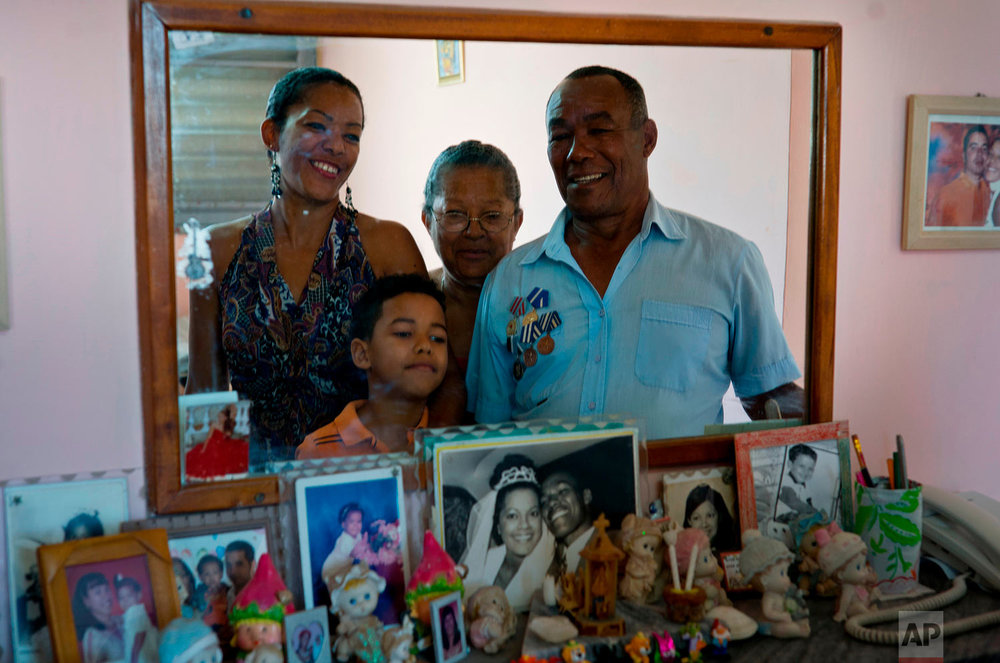 "In this April 14, 2018 photo, Amable Lopez, right, a Angola war veteran, poses with his family in Havana, Cuba. Lopez, a 69-year-old retiree, quit his university studies to join the team that built the famed, Soviet-style Alamar buildings. The former carpenter, firefighter and oil refinery worker said that compared to his generation's time, there is more development in Cuba and youths have everything they need to improve their lives. ""They need to improve the economy, raise salaries, lower prices. There are things that can be improved. Let's see what happens,"" Lopez said. (AP Photo/Ramon Espinosa)"