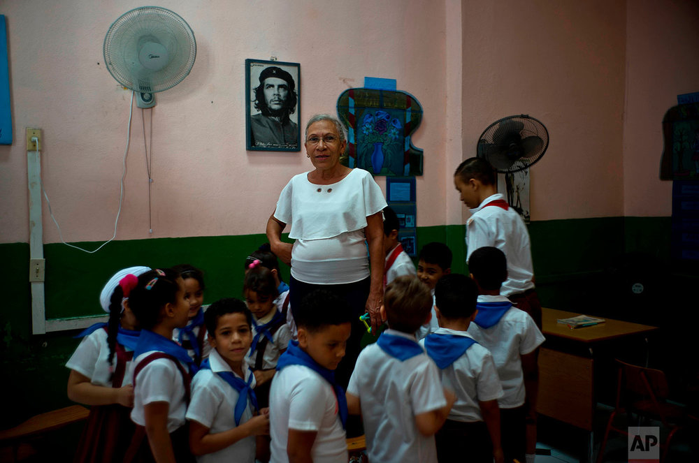 "In this April 13, 2018 photo, teacher Luisa Pacheco, 65, poses with her students in Havana, Cuba. Pacheco, who began teaching at the age of 14 in the Sierra Maestra's rural schools, said she likes education because she wants to train new generations for a good future and achieve what she did. When asked about Raul Castro's successor, she said ""I hope the new president will do what our commander Fidel Castro did,"" adding that she wants the U.S. to remove its embargo against Cuba to help improve the economy. (AP Photo/Ramon Espinosa)"