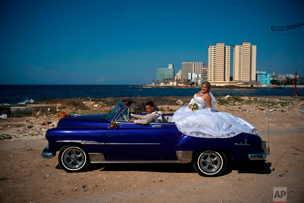 In this April 12, 2018 photo, newly-weds Dariel Verdecia, a 24-year-old computer engineer, and Roxana Cruz, a 26-year-old chemical engineer, pose for their wedding portraits in a vintage American car on the coast of Havana, Cuba. The couple said President Raul Castro's stepping down will be another step forward in Cuba's history, giving an entrance to new generations, and have hope the economy will continue growing. (AP Photo/Ramon Espinosa)