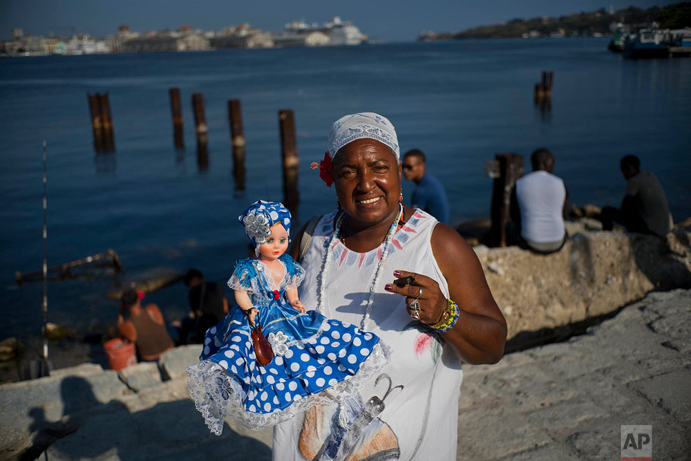 "In this April 13, 2018 photo, Santera Lourdes Nusa, 57, poses with her doll representing the Yoruba sea goddess ""Yemaya"" in Regla, across the bay from Havana, Cuba. Lourdes became a self-employed Santera at a very young age, reading people's futures. ""The world is subject to change. Our country has always adopted a policy of improving relations with the entire world,"" she said, adding Donald Trump's position toward Cuba will not change Cuba's position to open relations with the U.S. (AP Photo/Ramon Espinosa)"