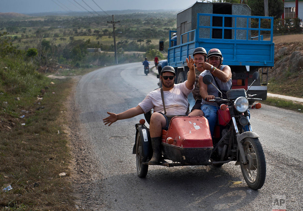 "In this April 13, 2018 photo, motorcycle taxi driver Ricardo Medina, 60, transports vegetable vender Rigoberto Herrera Mendez, left, and coconut vendor Osvaldo Ochoa in Campo Florido, east of Havana, Cuba. The three men expressed hope that new government leadership will improve things, saying the country cannot move backwards. ""We survive life with our work,"" said Medina. (AP Photo/Ramon Espinosa)"